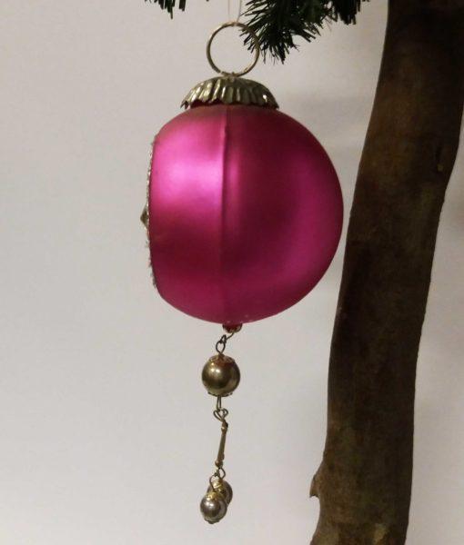 """Flot lyserød kugle dekoreret med similistens mønster og en """"hale""""."""