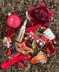 Rød julepynte pakke i julens farver med detaljer i guld. julepynt fra kugler til tog til mere anderledes julepynt såsom flasker til masker.