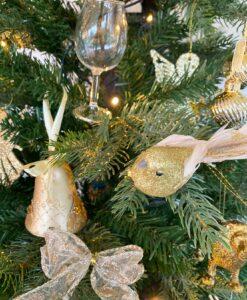 Stor julepynte pakke i guld. med en masse julepynt lige fra julekugler til ophæng og fugle til sløjfer.